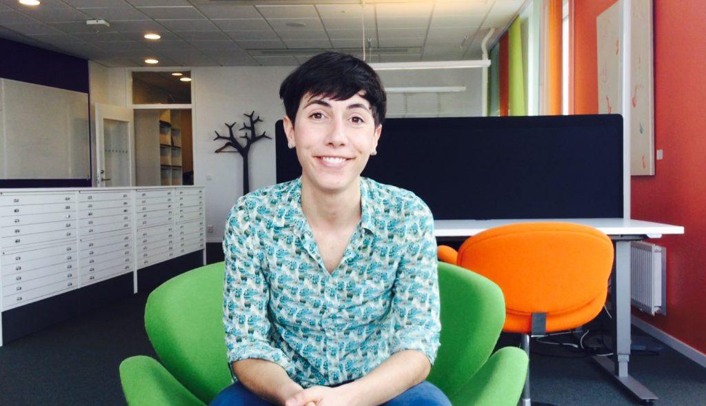 En bild på Anna Seravalli, sittande i en grön fåtölj i en kontorsmiljö.